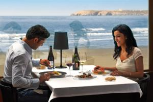 Enjoying a meal with wine at a restaurant close the Cantabrian Sea